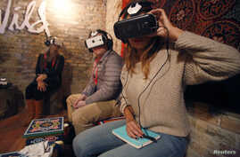 Members of the media try earphones and a headset used for virtual reality  at the Sundance Film Festival in Park City, Utah, Jan. 23, 2015.
