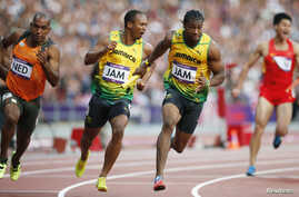 Jamaica's Yohan Blake (2nd R) takes the baton from teammate Michael Frater (2nd L) next to Netherlands' Giovanni Codrington (L) during the men's 4x100m relay round at the Olympic Stadium, August 10, 2012.
