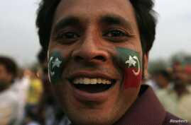A supporter of the political party Pakistan Tehreek-e- Insaf (PTI) with party flags painted on his face attends a rally in Lahore, March 23, 2013.