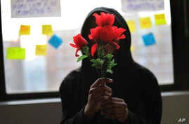 "A survivor of sexual assault holds plastic flowers after attending a meeting with the group ""Sisters in Strength"" in the Brooklyn borough of New York, March 14, 2019."