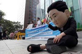 FILE - A South Korean university student wearing a mask depicting North Korean leader Kim Jong Un performs during a gathering to welcome the opening of the U.N. human rights office in Seoul, South Korea. A U.N. Commission of Inquiry report last year