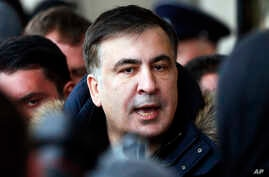 FILE - Former Georgian president Mikheil Saakashvili speaks with journalists near the Fairmont Grand Hotel in Kiev, Ukraine, Friday, Feb. 9, 2018. Saakashvili claimed that unidentified armed people wearing military uniform tried to arrest him inside
