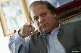 Nawaz Sharif, the leader of Pakistan Muslim League - Nawaz (PML-N) points as he speaks to foreign reporters at his residence in Lahore, May 13, 2013.