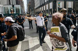 Police move protestors away from Trump Tower during a demonstration against President Donald Trump and his policies on immigration in New York, Sept. 19, 2017.