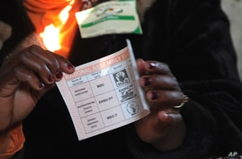 An electoral officer shows a ballot for House of Assembly candidates as the country went to the polls in a Harare suburb, July 31 2013.