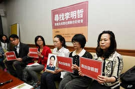 In this photo taken Friday, March 24, 2017, Lee Ching-yu, third from right holds up a photo of her missing husband and Taiwanese pro-democracy activist Lee Ming-che during a press conference with other representatives of non-governmental organization...
