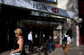FILE - People walk past an HSBC branch in Buenos Aires, Argentina, Nov. 28, 2014.