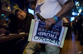 Mideast Israel 2016 US Election: An Israeli man holds a sign of U.S. presidential candidate Republican Donald Trump as he watches a live update with friends of the U.S. presidential election results at Mike's place bar in Jerusalem, Wednesday Nov. 9,...