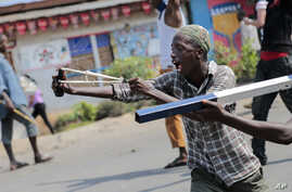 A demonstrator uses a slingshot during clashes with security forces in the Cibitoke district of the capital Bujumbura, Burundi Friday, May 29, 2015.