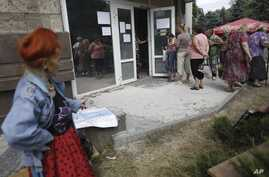 FILE - Local residents stand in line to get benefit payments outside the  rebel headquarters in Donetsk, eastern Ukraine, Aug. 19, 2014.