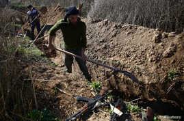 Fighters from the Free Syrian Army's Al Majd Brigades dig a trench in the rebel-held besieged area of al-Marj in the Eastern Ghouta of Damascus, Syria, Feb. 18, 2017.