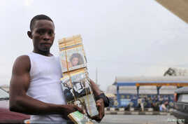 A boy sells a music CD along a road in NIgeria's oil hub city of Port-Harcourt July 8, 2010.