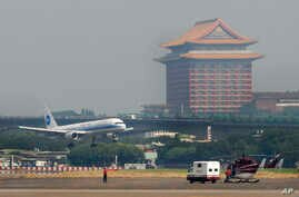 FILE - With the landmark Grand Hotel in rear, a plane carrying the first wave of mainland China tourists from the coastal city of Xiamen lands at the Taipei Airport, Friday, July 4, 2008, in Taipei, Taiwan.