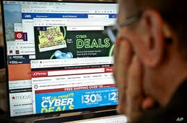 A journalist looks at a computer screen with webpages arranged to show Cyber Monday deals by various online retailers, Nov. 26, 2018, in New York.