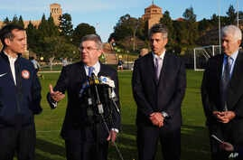 FILE - International Olympic Committee President Thomas Bach, second from left, is flanked by Los Angeles Mayor Eric Garcetti, left, LA 2024 chairman Casey Wasserman, second from right, and UCLA chancellor Gene Block, right, during a news conference