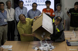 Occupy Central activists including Chung Kim-wah, left, and Robert Chung, right, empty a ballot box after a referendum on democratic reforms in Hong Kong, June 29, 2014.