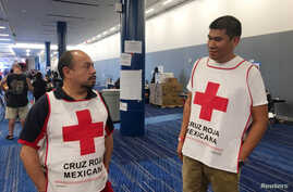 Marco Franco, left, deputy director of Mexican Red Cross disaster relief, talks with Gustavo Santillan who is part of a group of over thirty  Mexican Red Cross volunteers helping at the George R. Brown convention center in Houston, Texas, Sept. 4, 20