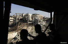 Palestinians look at the remains of a mosque, which witnesses said was hit in an Israeli air strike, in Gaza City, August 2, 2014.