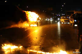 A police vehicle is set on fire by members of the Muslim Brotherhood and supporters of ousted Egyptian President Mohamed Morsi during clashes near a television production complex in Six October City in Giza, south of Cairo, August 2, 2013.