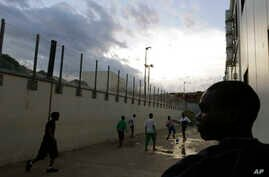 Migrants play soccer inside a temporary camp, after a fiery shipwreck of a fishing boat packed with 500 migrants from Eritrea, in Lampedusa, Italy, Oct. 6, 2013.