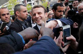 French independent centrist presidential candidate Emmanuel Macron shakes hands to supporters as he campaigns in Rodez, southern France, May 5, 2017.