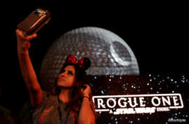 """A guest takes a selfie as the Spaceship Earth is turned into the Death Star via projectors in advance of the release of the new Star Wars movie """"Rogue One,"""" at the Walt Disney World's Epcot Center in Lake Buena Vista, Florida, U.S. Dec. 5, 2016."""
