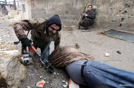 A Free Syrian Army fighter drags his comrade who was shot by sniper fire [and died soon after] during heavy fighting in the Ain Tarma neighborhood of Damascus, Syria, January 30, 2013.