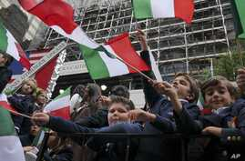 Schoolchildren wave Italian flags on a float in the Columbus Day parade in New York, Oct. 13, 2014. The parade is organized by the Columbus Citizens Foundation, and is billed as the world's largest celebration of Italian-American heritage and culture...