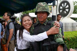 A pro-government demonstrator embraces a Thai soldier during a cleanup operation at a pro-government demonstration site on the outskirts of Bangkok, Thailand Friday, May 23, 2014. Thailand's ruling military on Friday summoned the entire ousted govern