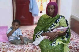 FILE - Meriam Ibrahim, sitting next to Martin, her 18-month-old son, holds the newborn daughter she gave birth to in jail in May at a prison in Khartoum, Sudan.