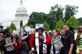 FILE - Rev. Dr. William Barber II, accompanied by Rev. Dr. Liz Theoharis and Rev. Jesse Jackson, speaks to the crowd outside of the U.S. Capitol during a Poor People's Campaign rally at The National Mall in Washington, June 23, 2018.