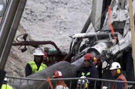 Rescue workers insert steel pipes to encase the escape tunnel that will be used to free trapped miners at the San Jose mine near Copiapo, Chile Sunday, Oct. 10, 2010.