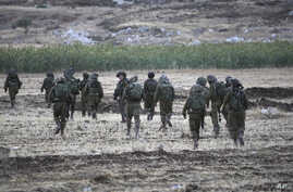 Israeli soldiers walk during an operation near Balata refugee camp in the West Bank city of Nablus,Tuesday, June 17, 2014.