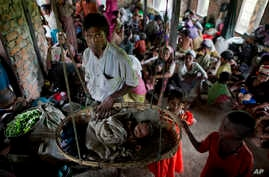 Internally displaced Rohingya people take shelter in a building ahead of the arrival of Cyclone Mahasen, in Sittwe, northwestern Rakhine State, Burma, May 15, 2013.