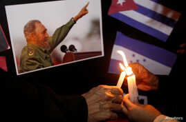 People place candles beside a picture of Fidel Castro, as part of a tribute, following the announcement of the death of the Cuban revolutionary leader, in Tegucigalpa, Honduras, Nov. 26, 2016.