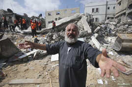 FILE - A  Palestinian man reacts as rescue workers search for victims under the rubble of a house, which witnesses said was destroyed in an Israeli airstrike, in Khan Younis in the southern Gaza Strip, July 29, 2014.
