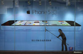 FILE - A worker cleans the windows in front of an iPhone 5C advertisement at an Apple store in Kunming, Yunnan province, China.
