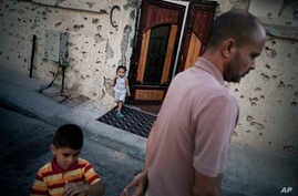 FILE -A Libyan family stands next to their house within Area 2 in Sirte , Libya, July 16, 2012. Sirte, the hometown of the country's late dictator Moammar Gadhafi and the last regime stronghold to fall during the revolution.