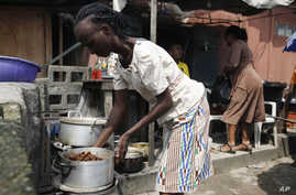 A woman prepares soup to sell on a street in Lagos, Nigeria, Aug. 7, 2014.