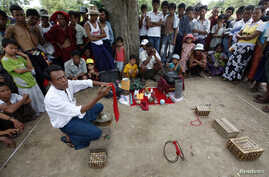 A magician performs during the Nat - or spirits - festival at Taungbyone village, near Mandalay, Burma, August 21, 2010.