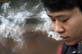 David Wang, 19, smokes outside during a break from classes at Seattle Central College in Seattle, Washington, Jan. 7, 2016.