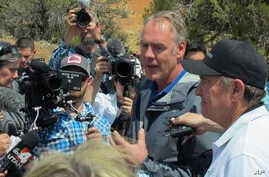 Interior Secretary Ryan Zinke, second from right, is joined by Utah Gov. Gary Herbert, right, during a press conference, May 8, 2017, at the Butler Wash trailhead within Bears Ears National Monument near Blanding, Utah.