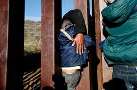 FILE - A Honduran migrant helps a youth squeeze through the U.S. border wall over to San Diego, California, from Playas in Tijuana, Mexico.