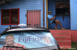 """An election poster for Voreqe """"Frank"""" Bainimarama can be seen in the rear window of a taxi as a man gestures from the doorway of a local gymnasium in the Fiji capital of Suva, Aug. 26, 2014."""