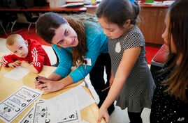 FILE - Language arts teacher Jennifer Walters helps students with their homework during an after-school program at Circleville Elementary School, in Circleville, Ohio, March 29, 2017.