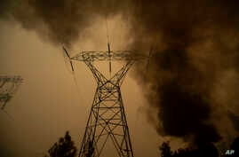 """Smoke billows around power transmission lines as the """"Camp Fire"""" burns in Big Bend, California, Nov. 9, 2018."""