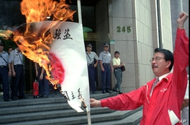 Chou Ching-chun burns a Japanese flag outside Japan's unofficial embassy in Taipei, Sept. 5, 1996 to protest Tokyo's claim to the Diaoyu Islands in the East China Sea.