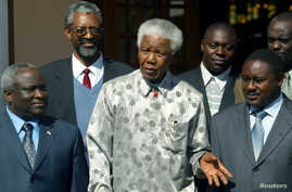 FILE - Former South African President Nelson Mandela, center, poses with President Domitien Ndayizeye, left, and Jean Minani, speaker of Burundi parliament, July 21, 2004.