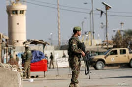 FILE - Afghan National Army (ANA) soldiers keep watch outside the Bagram Airfield entrance gate, after an explosion at the NATO air base, north of Kabul, Nov. 12, 2016.