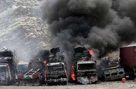 Smoke rises from NATO supply trucks following an attack by militants in Torkham, Afghanistan, Sept 2, 2013.